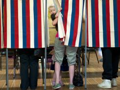 Landon Peterson peeks out of the voting booth while his mother Meghan votes in Metamora, Ill., in the state's March 20 primary.