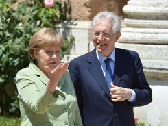 Italian Prime Minister Mario Monti, right, walks with German Chancellor Angela Merkel upon arrival for a meeting June 22, 2012 at Villa Madama in Rome.