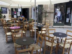 A man sits at an empty coffee shop in Old Nicosia in the Cypriot capital on June 22, 2012.