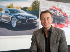 Elon Musk of Tesla with an image of the Model S at the company's Fremont, Calif., factory.