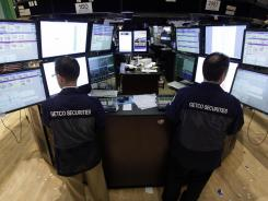 A pair of specialists work at their posts Friday on the floor of the New York Stock Exchange on Friday.