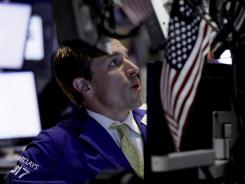 Trading specialist Christopher Trotta works on the floor of the New York Stock Exchange June 25, 2012.
