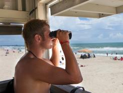 Lifeguard Dalton Gull keeps an eye on swimmers May 29 at Atlantic Beach, N.C.