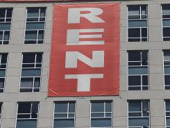 A large &quot;Rent&quot; banner is posted on the side of an apartment building in San Francisco.