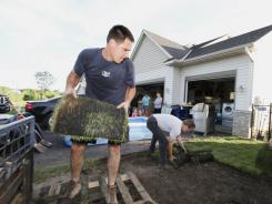 Mike Resop, left, finishes sodding his home June 25 in New Market, Minn.