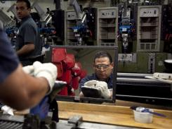 Worker Renaldo Escobar, of Boston, center, presses a shoe onto a last during the assembly process at the New Balance Athletic Shoe factory in Boston.