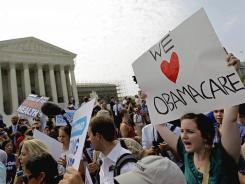 Supporters of President Obama's health care law celebrate outside the Supreme Court in Washington, D.C., on June 28, 2012.