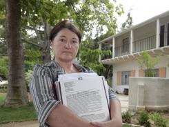 DeAun Tollefson holds the notice of trustee sale, outside her foreclosed home in Sacramento, Calif., in June 2012.