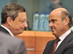 European Central Bank president Mario Draghi, left, speaks with Spanish Finance Minister Luis De Guindos before a Eurozone meeting at European Union Headquarters in Brussels July 9, 2012.