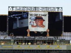 Workers make improvements on a new scoreboard at Lambeau Field, home of the NFL football Green Bay Packers June 27, 2012. On the big screen is a caricature of former Packers coach Vince Lombardi holding the Super Bowl trophy that bears his name.