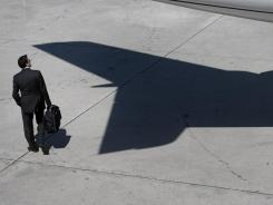 A visitor walks past the shadow of a business jet's tail in May 2012 at the European Business Aviation Convention and Exhibition in Geneva.