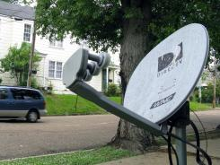A mini-van passes a DirecTV satellite dish in a residential area adjoining downtown Jackson, Miss.