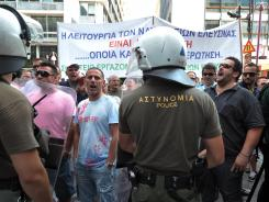 Shipyard workers demonstrate in front of police protecting the Finance Ministry in Athens on Tuesday. Workers demonstrated against unemployment in their sector.