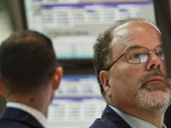 Douglas Johnson, a trader for Getco Securities from Levittown, Pa., works during early trading at the New York Stock Exchange in July 2012.
