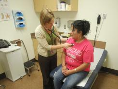 Physician assistant Anna Streuli examines Maria Guzman at Multnomah County's Mid-county Health Center, in Portland, Ore.
