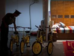 A security guard tries a bicycle during a consumer products exhibition in Beijing July 13, 2012.