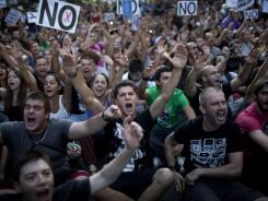 Demonstrators shout slogans during a protest in Madrid on Friday condemning the recent austerity measures announced by the Spanish government.