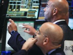 Traders work at the start of early trading at the New York Stock Exchange July 10, 2012.