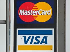 Visa and MasterCard credit card logos in a store window in Washington, D.C.