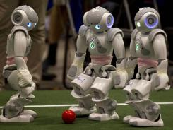Robots vie for the ball during a robot soccer match at the RoboCup 2012 in Mexico City. Thousands of participants came to the event to show off their soccer robots, rescue robots and service robots.