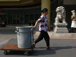 A woman pulls a cart with a trash bin past a hotel entrance in Beijing, July 16, 2012.