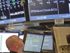 Peter Giacchi, a floor official and trader at Getco Securities, monitors JPMorgan trades at the New York Stock Exchange July 13, 2012.