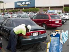 A man cleans a car in the parking lot of a Walt-Mart Super Center in Mexico City in April 2012.