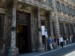 People walk in front of Unicredit bank in downtown Rome on May 15, 2012.