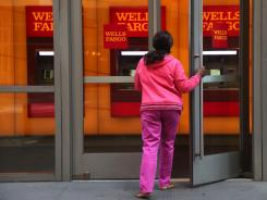 A woman enters a Wells Fargo bank in New York in May 2012, when credit card debt showed the biggest one-month rise in more than four years.