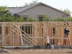 Workers frame a home in a new community in Gilbert, Ariz. Real estate experts say the Phoenix metro housing market is recovering faster than other U.S. cities.