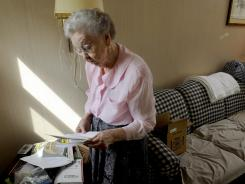 Mary Cate Jones, 78, reads an eviction notice at her home near Knoxville, Tenn. on Tuesday, May 15, 2012. She took out a loan against the home and then fell behind on mortgage payments after hip surgery about three years ago, then the home went into foreclosure.