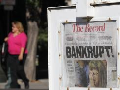 "A pedestrian walks by a Stockton Record newspaper rack displaying the headline ""Bankrupt!"" on June 27, 2012, in Stockton, Calif. Members of the Stockton city council voted to adopt a spending plan for operating under Chapter 9 bankruptcy protection."