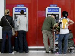 Travelers withdraw cash from ATM machines at Heathrow Airport on Wednesday as London prepares for the 2012 Summer Olympics.