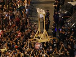Demonstrators hold a mock guillotine with a banner reading 'Thieves' cutter' during a protest against austerity measures announced by the Spanish government in Madrid, July 19, 2012.