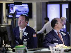 Specialists Charles Boeddinghaus, left, and Douglas Johnson, work at their posts on the floor of the New York Stock Exchange on July 17, 2012.
