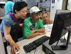 Career center specialist Sun Gaddis, left, helps job seeker Kaston Joshua, while Rudy Martin looks on at WorkSource Oregon in Tualatin, Ore. July 17, 2012.