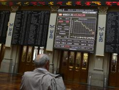 A man watches the Ibex 35 index at Madrid's stock exchange, on July 20, 2012.