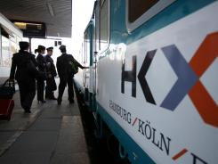 Train guards enter the carriage before the departure of the first Hamburg-Koeln-Express (HKX) July 23, 2012.