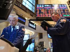 Mark Zifchak, left, and Johnathan Corpina, both of Meridian Equity Partners, trade on the floor of the New York Stock Exchange, July 23, 2012 in New York.