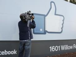 A cameraman shoots the 'Like' sign outside of Facebook headquarters in Menlo Park, Calif.