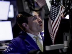 Specialist Christopher Trotta works on the floor of the New York Stock in this June 25, 2012, photo.