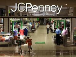Shoppers walk in a JC Penney story in Plano, Tex., June 19, 2012.