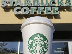 A cup of Starbucks coffee sits outside a shop in Cambridge, Mass.