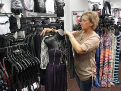Vanity store manager Sheri Ludlow dresses a mannequin July 25, 2012, at the Tippecanoe Mall in Lafayette, Ind. Consumer spending was weak in the second quarter.