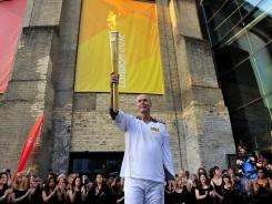 Sir Clive Woodward holds the Olympic Flame in London July 26, 2012, day 69 of a 70-day relay.