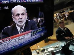 Federal Reserve Chairman Ben Bernanke's testimony before Congress is shown on a television screen on the trading floor of the New York Stock Exchange.