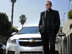 Former General Motors Joel Ewanick vice president for U.S. marketing poses with a Chevy Cruze.