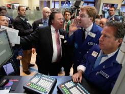 Traders and specialists work on the floor of the New York Stock Exchange on July 17, 2012.
