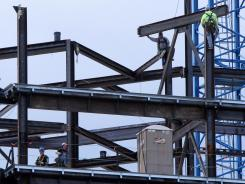Ironworkers lower a girder during construction of a dormitory building on the University of Pittsburgh campus in May.