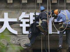 Workers arrange the Chinese sign of a bank in Shanghai.